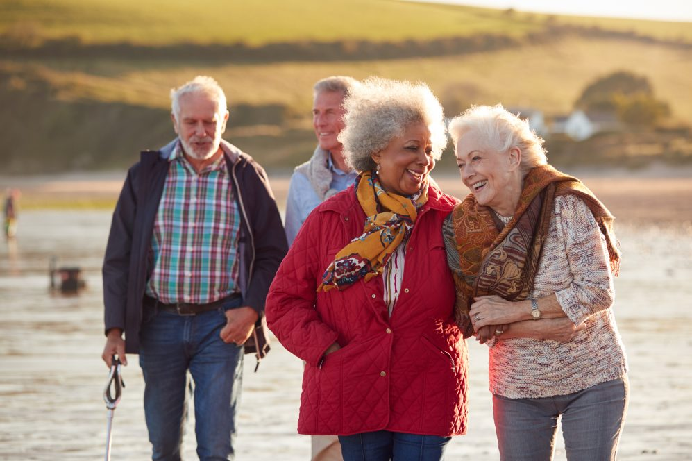 Group Of Smiling Senior Friends Walking Arm In Arm Along Shoreline