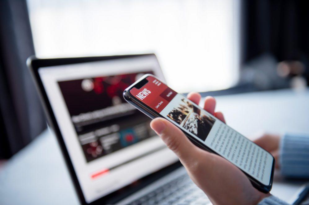 main tenant un téléphone avec un site d'actualités en ligne