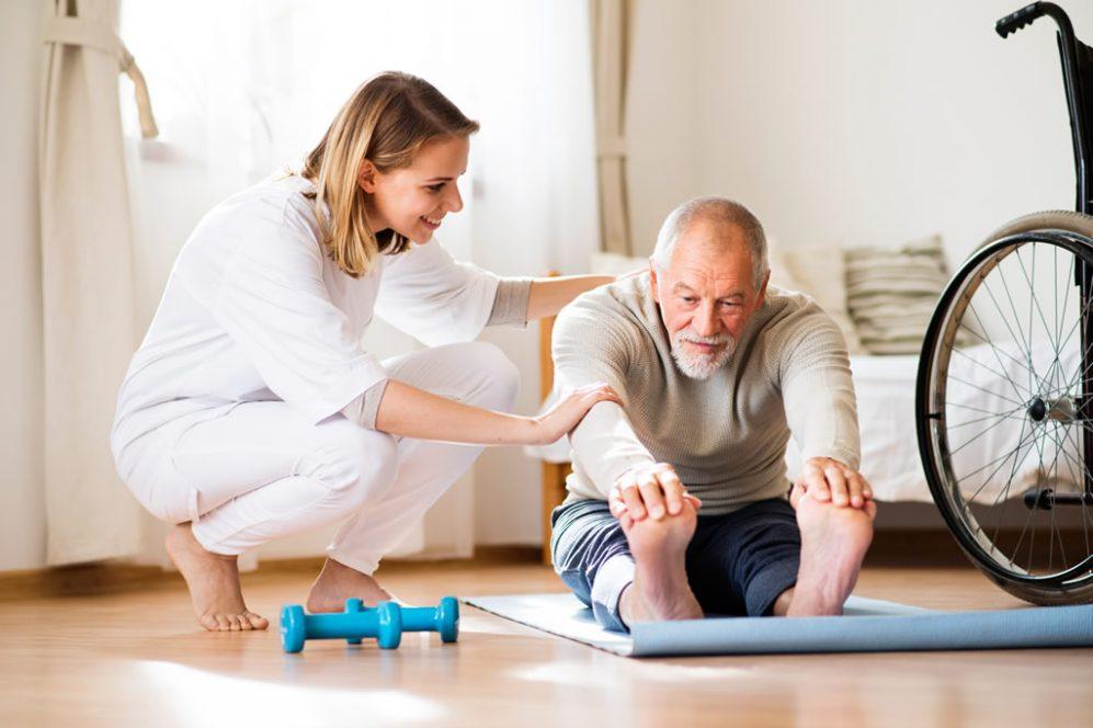 Physical therapist helping senior man stretch