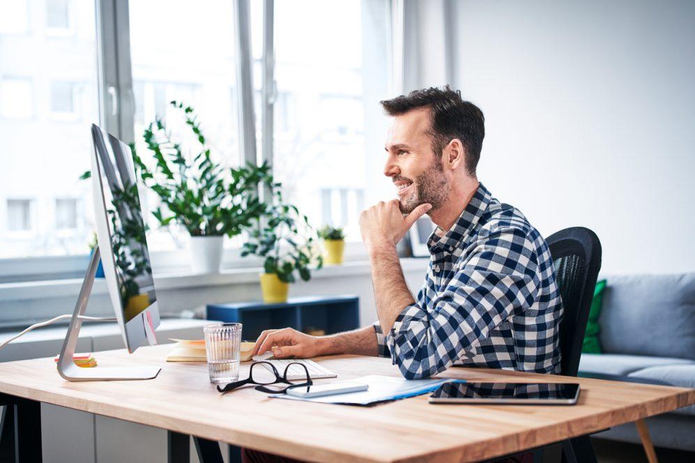 homme adulte souriant à l'ordinateur
