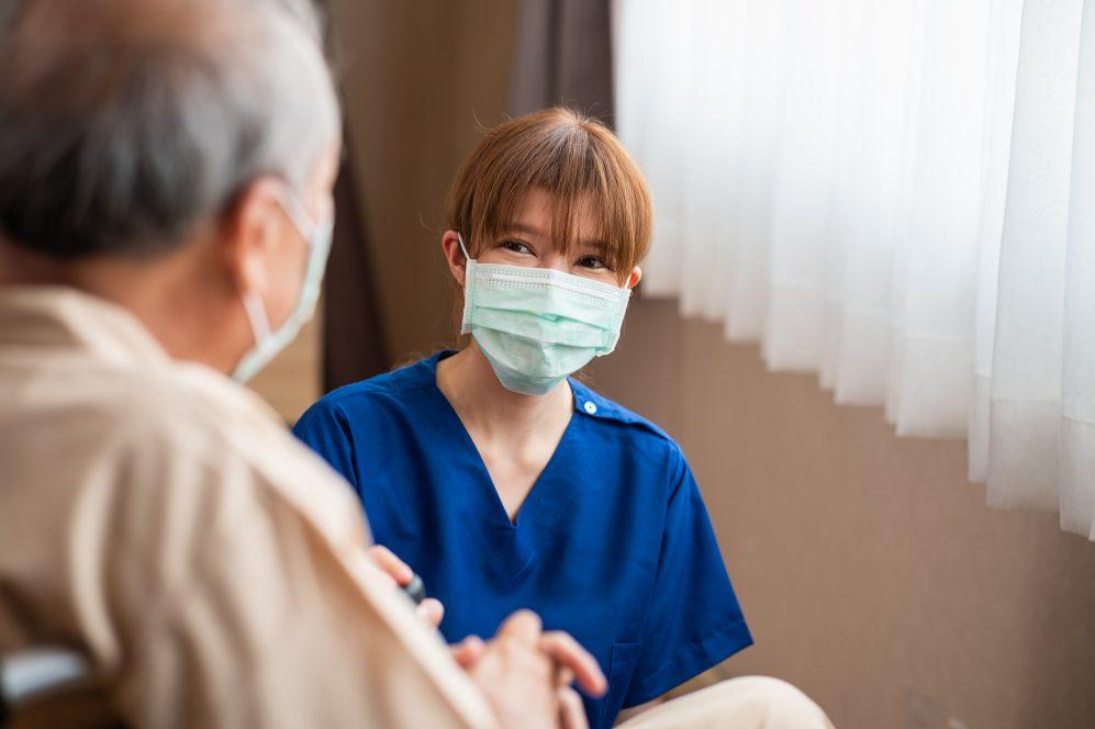 jeune infirmière agenouillée à côté d'un patient plus âgé