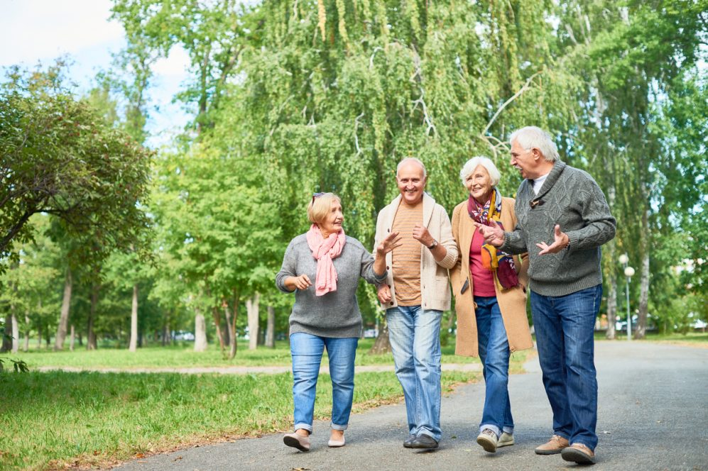 Group of seniors walking and talking in park