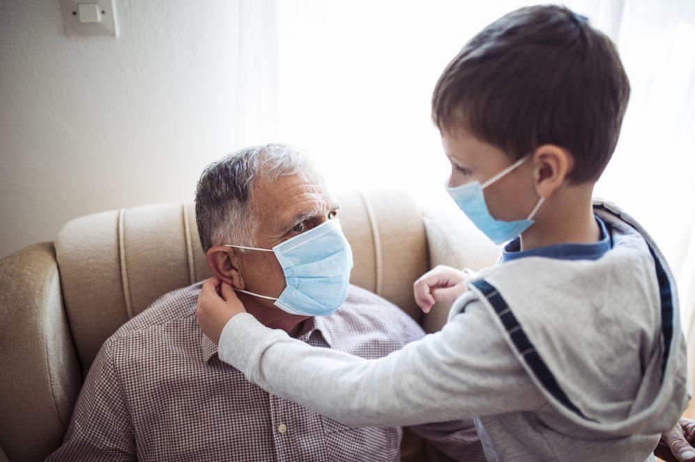 enfant aidant un homme âgé à mettre un masque