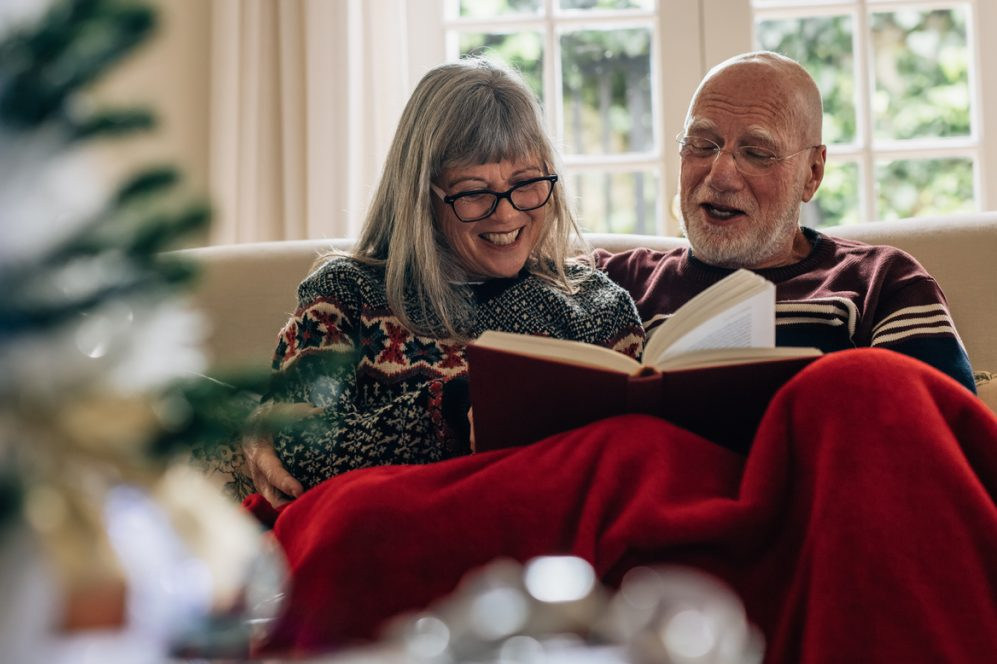 Adult couple happily reading book