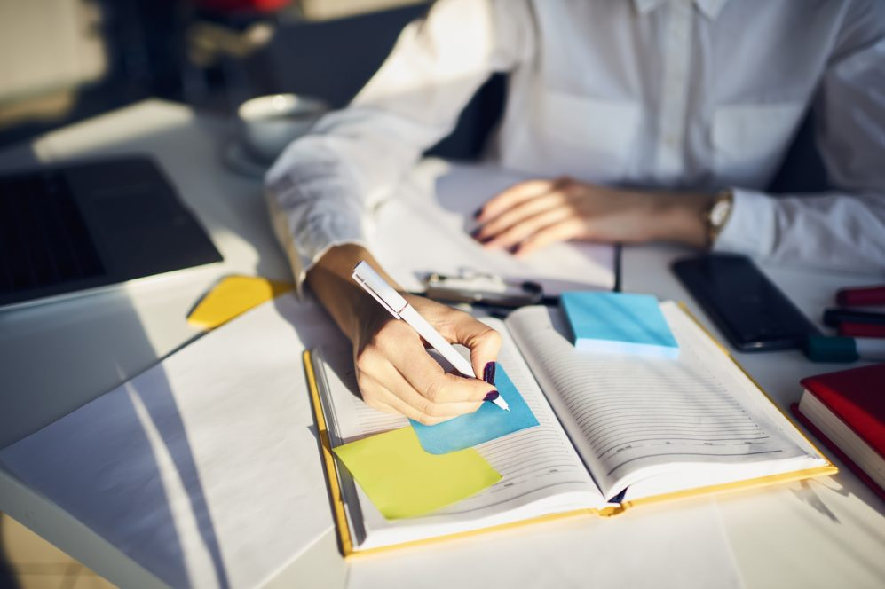 Professional woman writing on sticky note