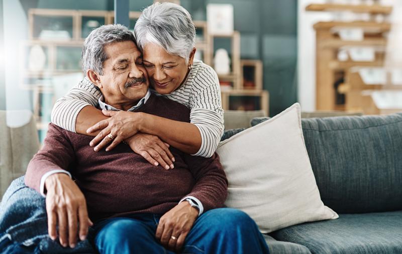cheerful elderly woman hugging her husband