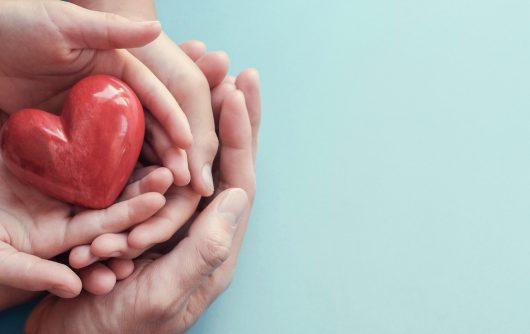 Mains adultes et enfants tenant un coeur rouge