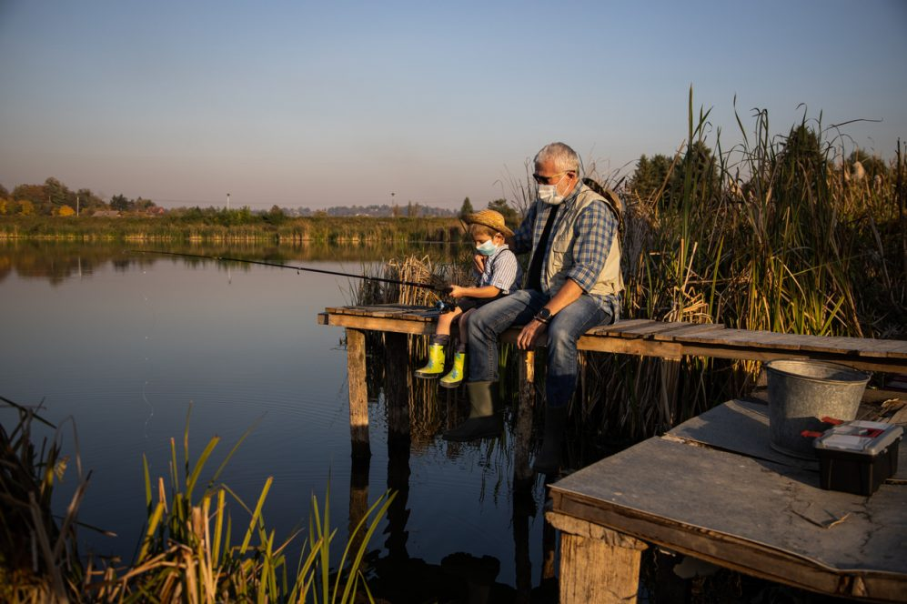 Senior man sitting on jetty fishing in lake with grandson under covid masks