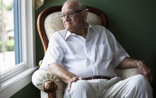 Senior Man sitting in chair looking out window