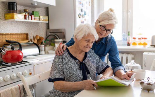 Femme mûre aidant la mère âgée avec la paperasse