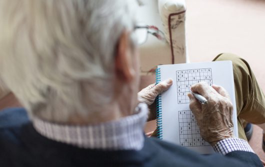 enior Man Doing Sudoku Puzzle At Home